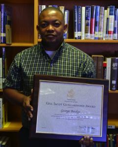 George Beukes holding framed award